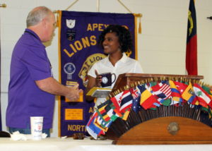 Lion Tony presents speaker Tomeico with a Lions Club mug