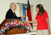 PDG Andy Lilliston hands Lion Jolene the gavel